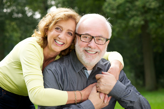 Hugging, middle-aged couple posing for picture