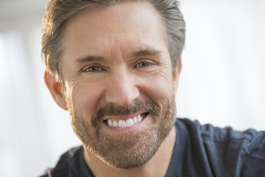 Smiling man with gray hair and beard
